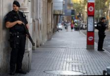Armed Catalan Mossos d'esquadra officers stand guard at Las Ramblas street where a van crashed into pedestrians in Barcelona
