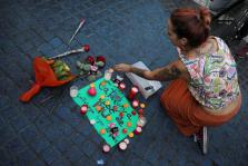 "A woman places a candle on a placard, reading in Spanish and Catalan ""Catalonia, place of peace"", in the area where a van crashe"