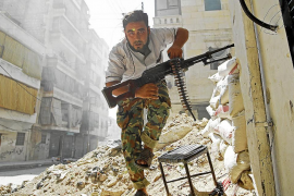 A Free Syrian Army fighter takes cover during clashes with Syrian Army in the Salaheddine neighbourhood of central Aleppo