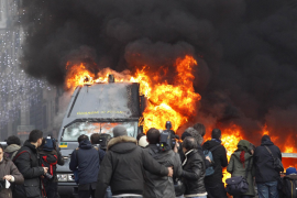 A Guardia di Finanza vehicle burns near the parliament during anti-government clashes in Rome