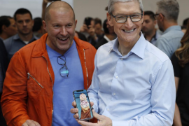 Apple CEO Cook plays with an iPhone during a launch event in Cupertino