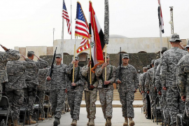 Members of the U.S. military retire its ceremonial flags signifying the end of their presence in Iraq at the Baghdad Diplomatic
